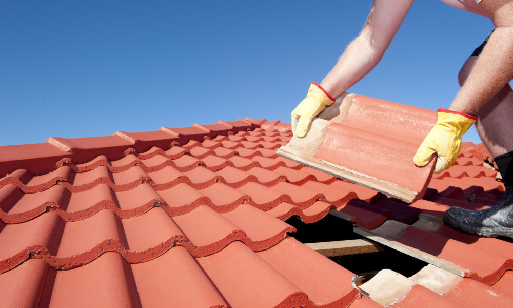Roof repair, worker with yellow gloves replacing red tiles or shingles on house with blue sky as background and copy space.