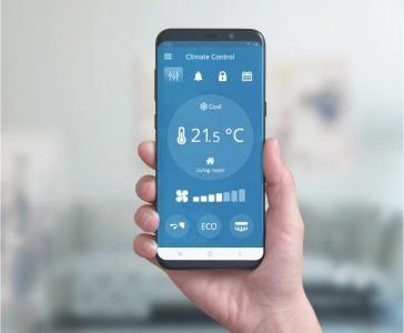 Smart phone in hand with climate control app. Concept of environmental comfort automation with a simple phone app.